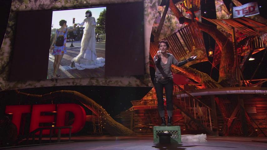 Extrait de la présentation TED d'Amanda Palmer. On la voit perchée sur une caisse de marché, un chapeau avec un billet à ses pieds. Elle se penche vers le public une fleur à la main. Au fond, l'écran montre une photo d'elle déguisée en mariée effectuant le même geste vers une passante.